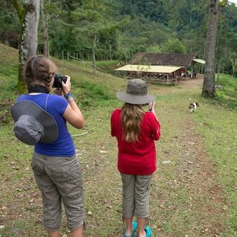 Due ragazze di scattare foto con le macchine fotografiche digitali in una fattoria, finca el cisne, honduras