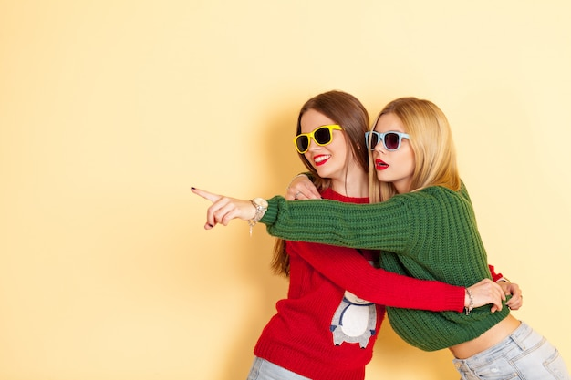 Due ragazze divertenti bei pantaloni a vita bassa in spettacoli di occhiali da sole e maglioni
