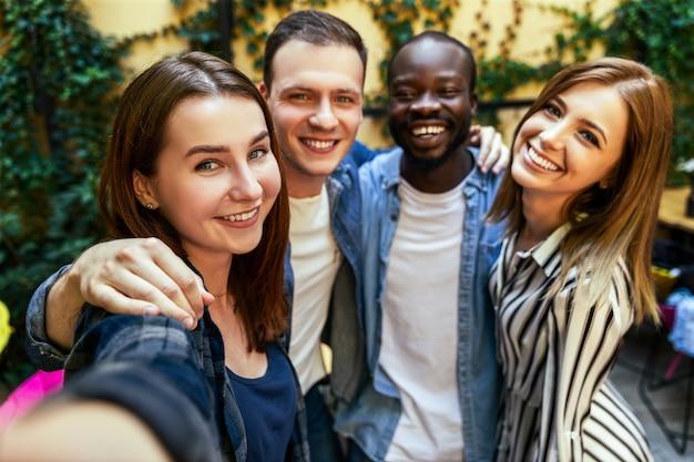 Due ragazze e due ragazzi stanno scattando selfie all'aperto, si abbracciano e con sorrisi sinceri