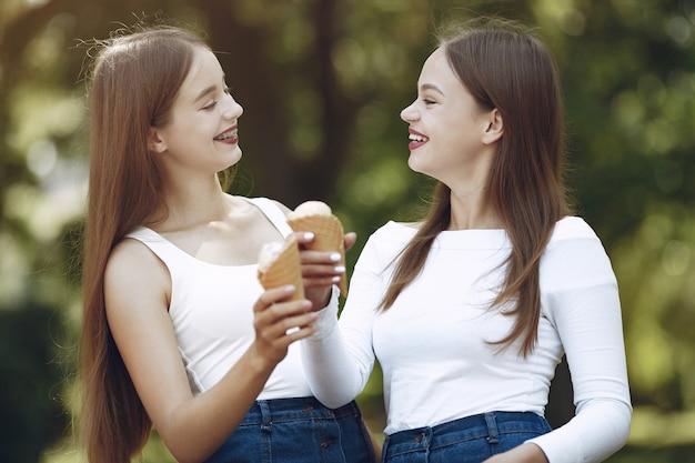 Due ragazze eleganti e alla moda in un parco di primavera