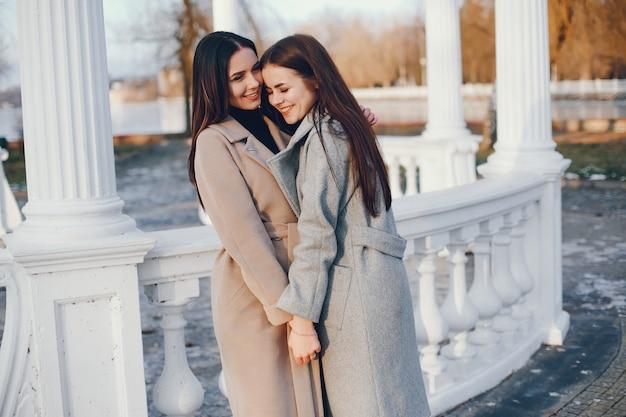 Due ragazze eleganti riposano in una città