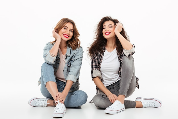 Due ragazze felici che si siedono insieme sul pavimento sopra la parete bianca