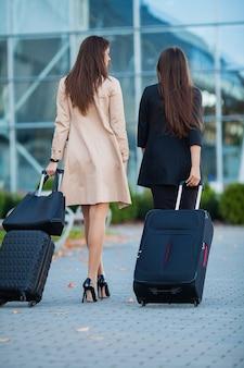 Due ragazze felici che viaggiano insieme all'estero, portando i bagagli in valigia in aeroporto