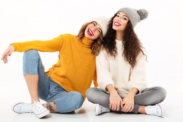 Due ragazze felici in maglioni e cappelli che si siedono insieme sul pavimento sopra la parete bianca