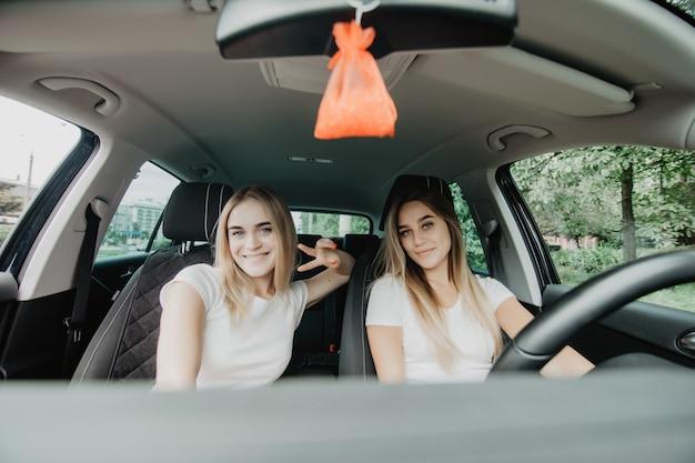 Due ragazze felici seduti in macchina e gesticolano il segno della vittoria si divertono mentre fanno un viaggio in auto