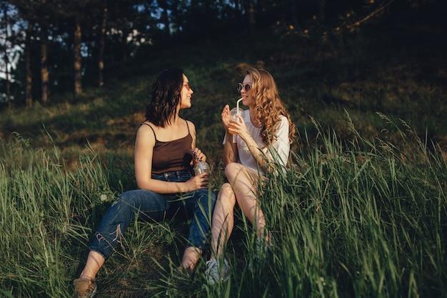Due ragazze felici si divertono, si siedono sull'erba, bevono cocktail dal bicchiere di plastica con la cannuccia in occhiali da sole, al tramonto, espressione facciale positiva, all'aperto