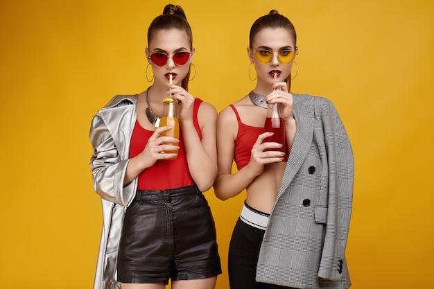 Due ragazze gemelle di hipster glamour elegante in top rosso moda con cocktail drink