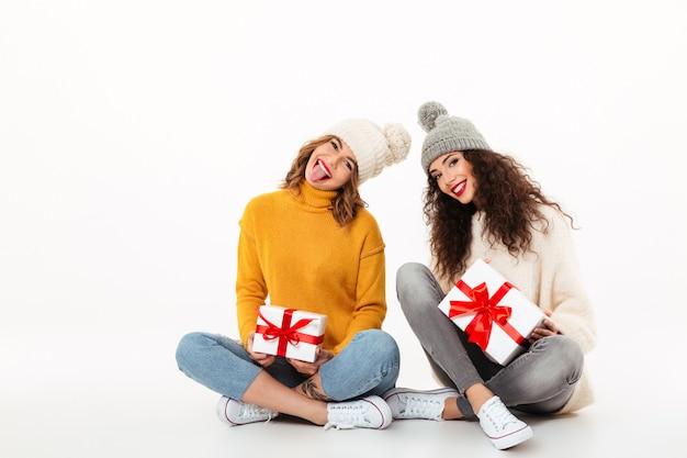 Due ragazze giocose in maglioni e cappelli seduti con regali sul pavimento insieme sul muro bianco