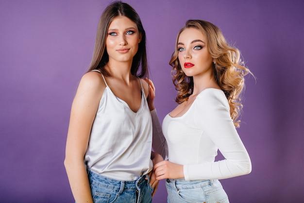 Due ragazze giovani e belle mostra emozioni e sorrisi in studio su uno sfondo viola. ragazze per la pubblicità.