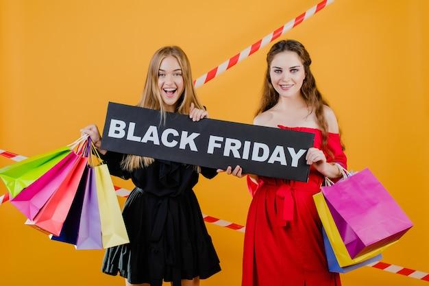 Due ragazze graziose sorridenti hanno il segno nero di venerdì con i sacchetti della spesa variopinti e il nastro segnaletico isolati sopra giallo