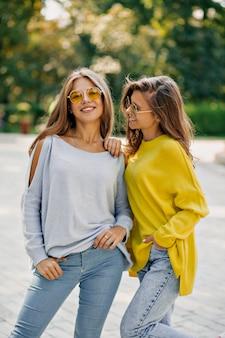 Due ragazze hipster divertenti felici con occhiali luminosi e pullover, trascorrono il tempo libero all'aperto, abiti estivi luminosi e accessori,