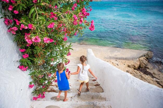 Due ragazze in abiti blu divertirsi all'aperto. bambini alla strada del tipico villaggio tradizionale greco con pareti bianche e porte colorate sull'isola di mykonos, in grecia