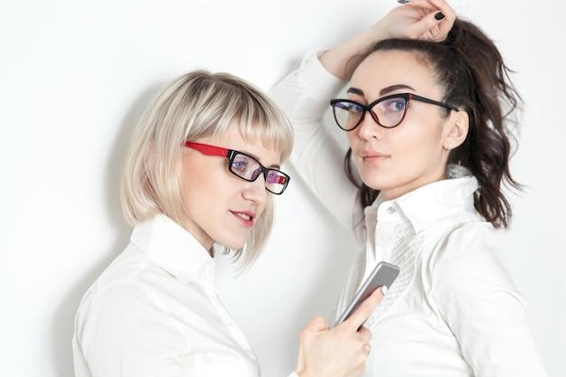 Due ragazze in camicie bianche e occhiali fanno selfie al telefono