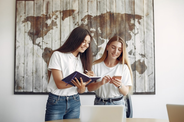 Due ragazze in magliette bianche che lavorano in ufficio