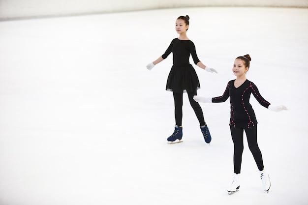 Due ragazze in posa sulla pista di pattinaggio
