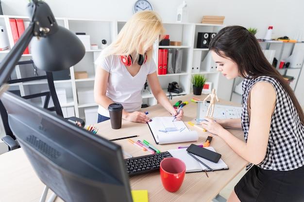 Due ragazze lavorano in ufficio. la ragazza tiene in mano un modello di uomo.