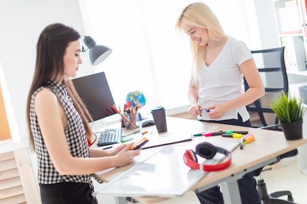 Due ragazze lavorano in ufficio. ragazza in possesso di un telefono.