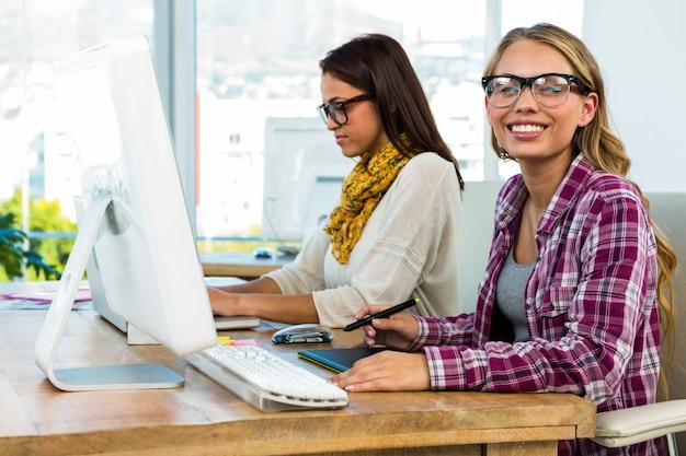 Due ragazze lavorano in ufficio su computer e tablet
