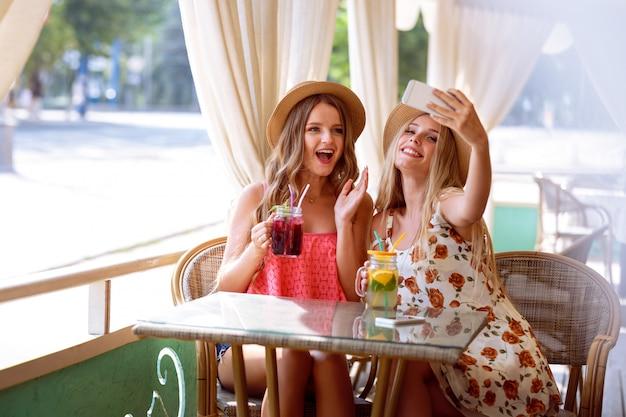Due ragazze positive fanno selfie al telefono mentre sono seduti nel parco giochi estivo in un caffè