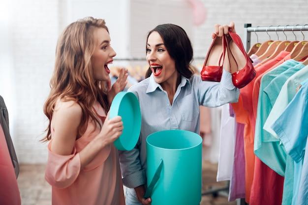 Due ragazze scelgono vestiti nel negozio.