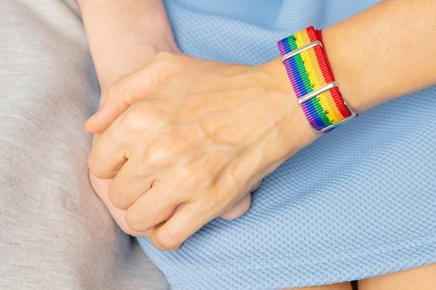 Due ragazze si tengono per mano, da una parte c'è il braccialetto lgbt. il concetto di amore, tolleranza sessuale, omosessualità.