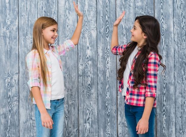Due ragazze sorridenti che stanno contro la parete di legno grigia che dà livello cinque