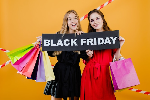 Due ragazze sorridenti graziose hanno il segno nero di venerdì con i sacchetti della spesa variopinti e il nastro segnaletico isolati sopra giallo