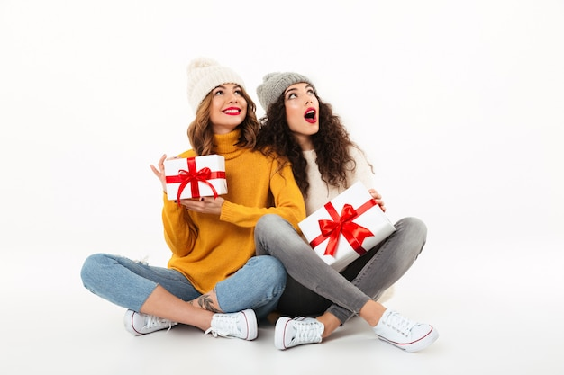 Due ragazze sorridenti sorprese in maglioni e cappelli che si siedono insieme con i regali sul pavimento mentre guardano su sopra la parete bianca