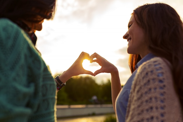Due ragazze stanno mostrando il cuore dalle mani al tramonto