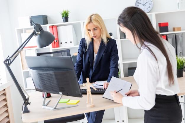 Due ragazze stanno nell'ufficio vicino al tavolo e lavorano con i documenti.
