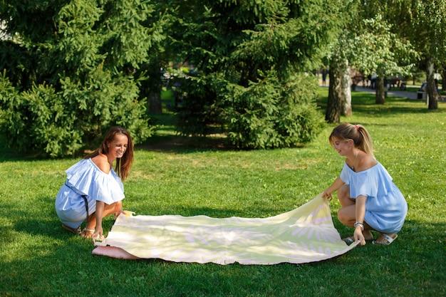 Due ragazze su un prato verde stendono una coperta da picnic