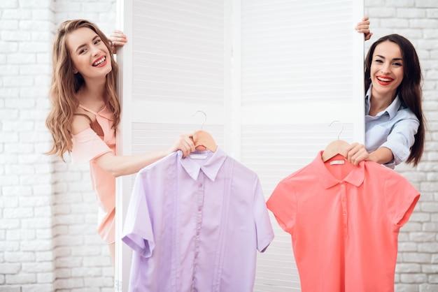 Due ragazze sullo shopping scelgono i vestiti nel negozio.
