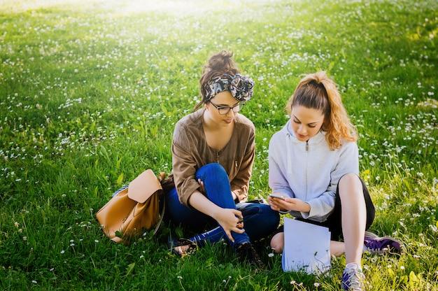 Due ragazze sylish seduto sull'erba e utilizzando il telefono