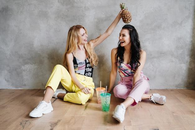 Due ragazze, una bruna e una bionda, in pantaloni colorati. mangia ananas e bevi cocktail.