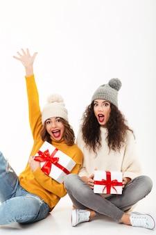 Due ragazze urlanti verticali in maglioni e cappelli che si siedono insieme con i regali sul pavimento sopra la parete bianca