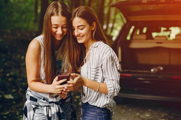 Due ragazze vicino all'automobile
