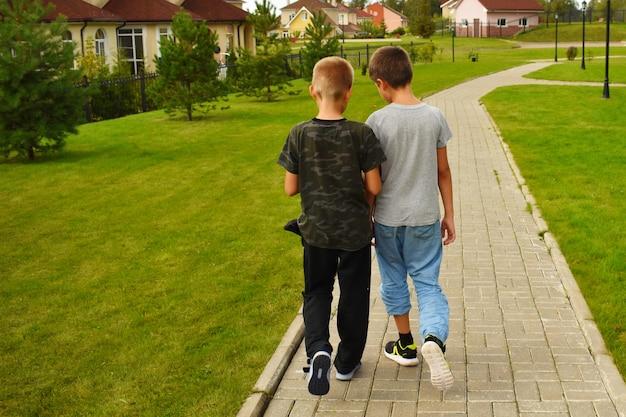 Due ragazzi amici vanno lungo il sentiero in estate. amicizia per bambini.