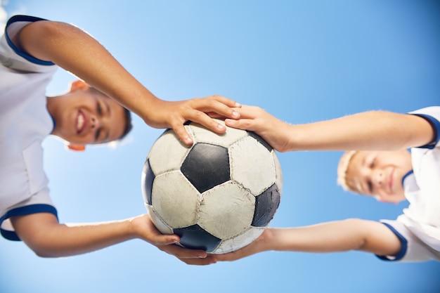 Due ragazzi che tengono la palla di calcio