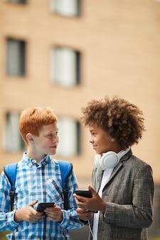Due ragazzi che usano i loro telefoni intelligenti