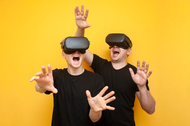 Due ragazzi con i moderni occhiali vr giocano su uno sfondo giallo, un paio di amici di giocatori con gli occhiali per realtà virtuale