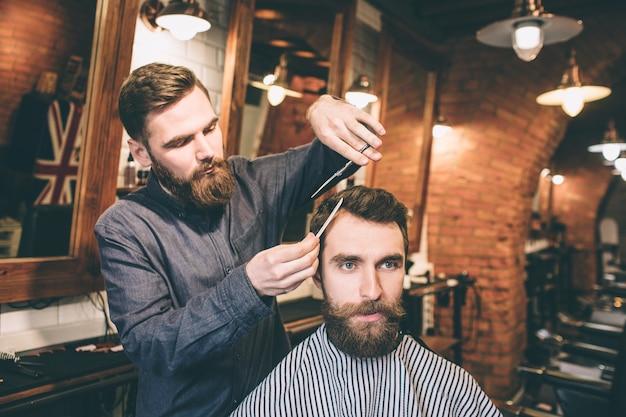 Due ragazzi con la barba sono in un barbiere. il parrucchiere sta tagliando i capelli del suo cliente usando le forbici e una piccola spazzola per capelli.