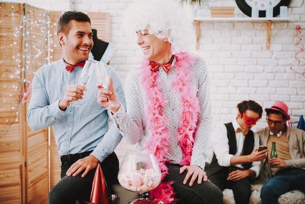 Due ragazzi gay sorridenti in cravatte che flirtano scherzosamente alla festa.