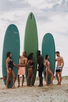 Due ragazzi in spiaggia tiene surf. ragazze in costume da bagno.