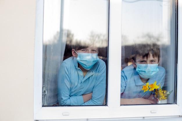 Due ragazzi nelle maschere mediche della procedura del ciclo dell'orecchio guardano fuori dalla finestra della casa. i bambini rimangono a casa durante la pandemia di coronavirus in quarantena.