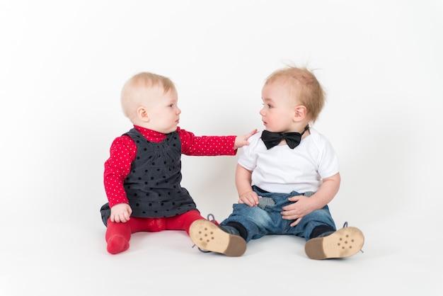 Due ragazzi seduti sullo spazio bianco che si guardano l'un l'altro