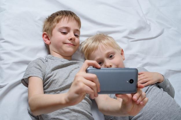 Due ragazzi sono sdraiati a letto con uno smartphone. gadget leisure