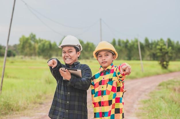 Due ragazzo che indossa casco ingegnere tenendo la compressa in piedi all'aperto