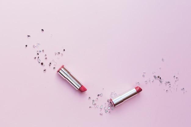 Due rossetti rosa con pezzi di vetro schiacciato su sfondo rosa