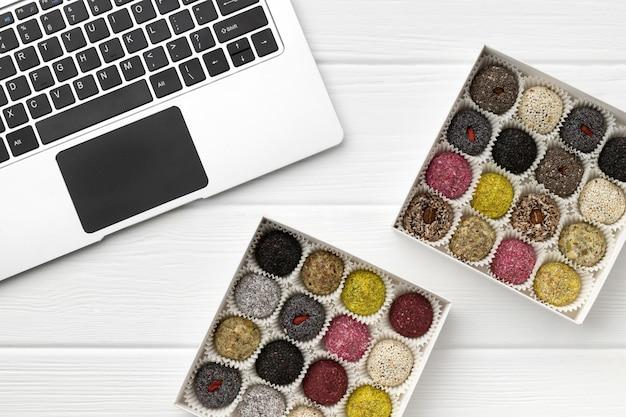 Due scatole di dolci vegani sfere di energia vicino al computer portatile sul tavolo di legno bianco