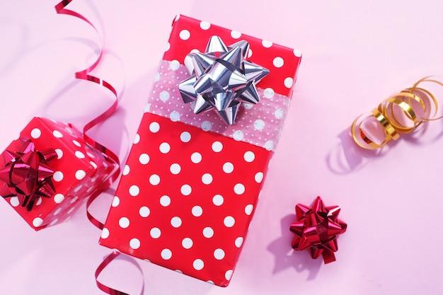 Due scatole regalo rosse a pois bianchi e un fiocco in argento e rosso, serpentino rosso e oro, fiocco rosso su rosa